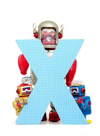 capital letter X held by vintage robot toys Stock Photo