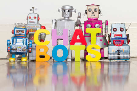 The word CHAT BOTS with retro robots on a wooden floor with reflection Stock fotó