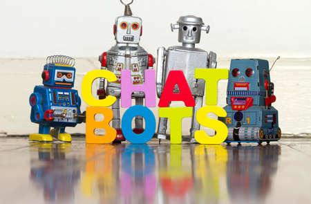The word  CHAT BOTS with 4 retro robots on a wooden floor with reflection