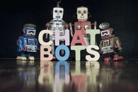 The word  CHAT BOTS with retro robots on a wooden floor with reflection toned Stock fotó
