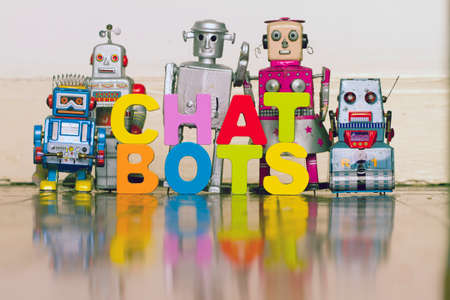 The word  CHAT BOTS with 5 retro robots on a wooden floor with reflection Archivio Fotografico