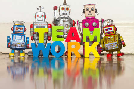 The word TEAM WORK with wooden letters and 5 retro bots on a wooden floor say hi