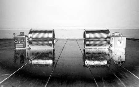 retro robots on tin can phones on a wooden floor with reflection  solarized monochrome