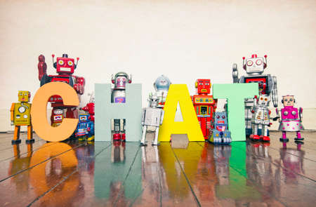 robots hold up the word CHAT  on an pld wooden floor