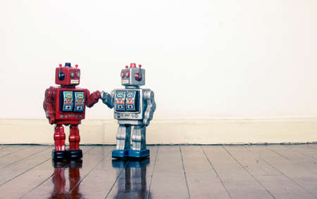 big red and silver robots holding hands with love on an old wooden floor copy space