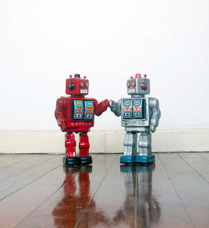 big red and silver robots holding hands with love on an old wooden floor