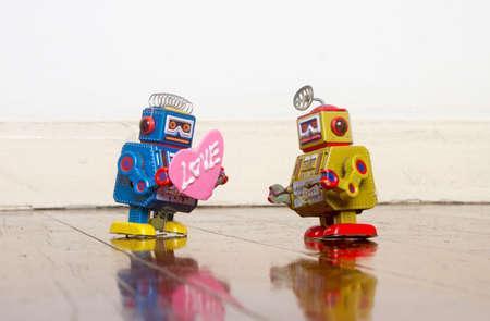 little blue robot giving a bog pink love heart  on a old wooden floor