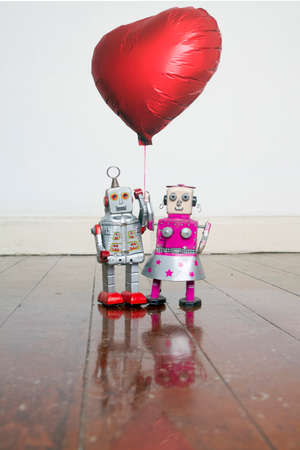 two robots in love  bouth holding a red balloon standing on a old wooden floor