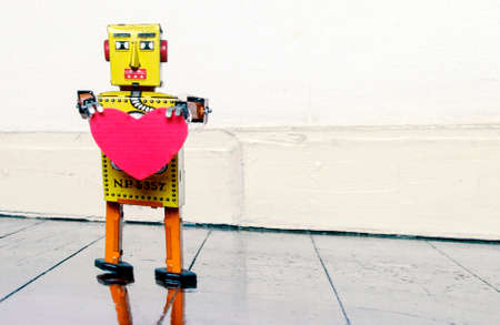 retro yellow robot holding a red  heart  standing on a old wooden floor with copy space