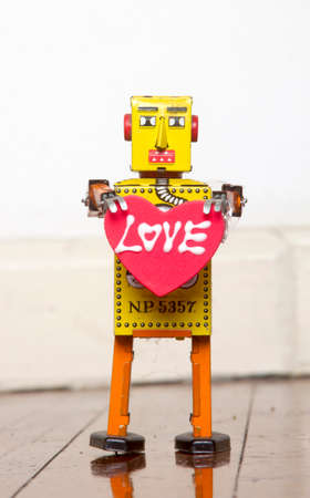 retro yellow robot toy holding a red  heart with love