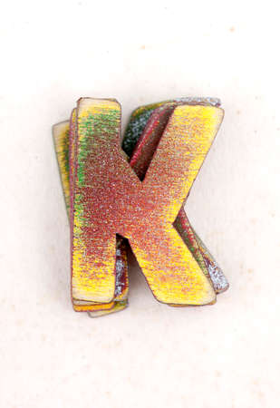 a pile of old  painted wooden letters K , s on old worn paper Stock Photo