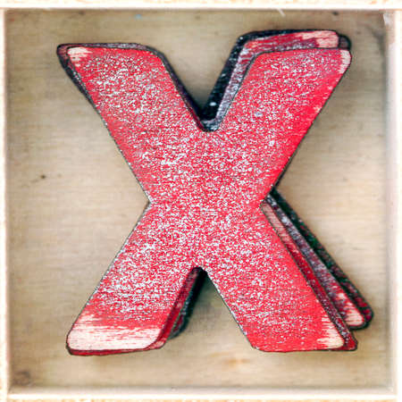 old wooden letter  X in a box shot from above macro image