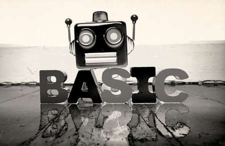 robot head and the word BASIC on a old wooden floor  solarized  monochrome