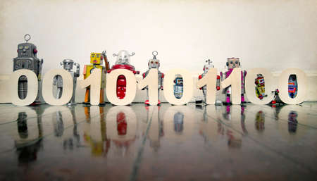 a line of retro bots on a wooden floor with 0,s and 1,s binary code numers Imagens