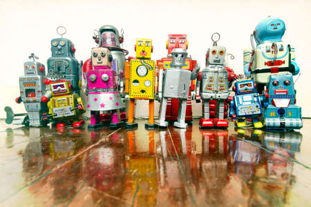 a large group of retro tin robot toys on a old wooden floor  with reflection