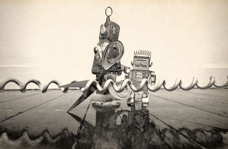 two robots cut the phone line  on a wooden floor ,solarized monochrome