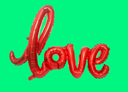 red foil balloon isolated on bright green