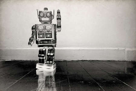 retro robot waving on a wooden floor solarized  toned monochrome image Imagens