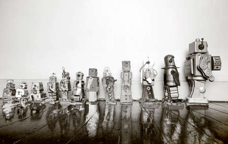a line of vintage robots from small to big in solarized monochrome
