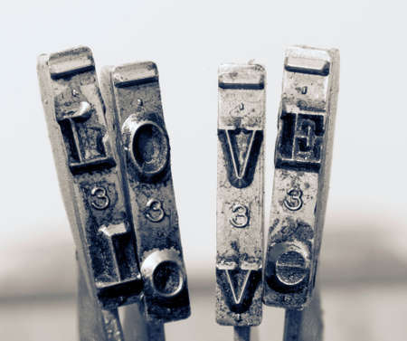 the word love with old typewriter hammers macro in monochrome