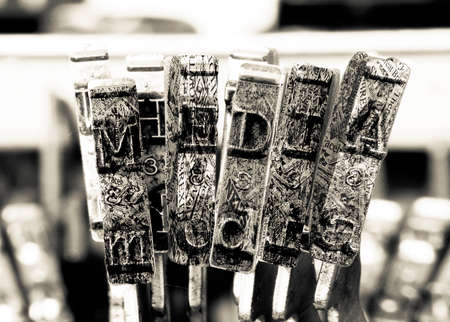 the word MEDIA with old typewriter hammers  in monochrome Фото со стока