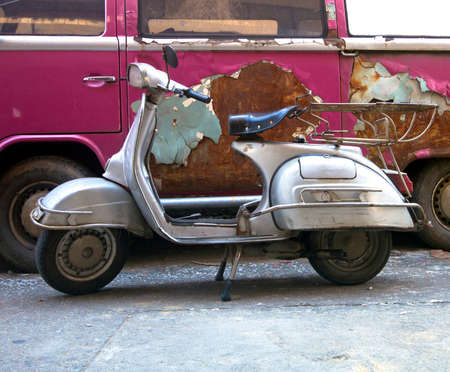 old scooter in front of a old van  on the street Imagens