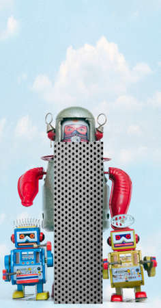 retro robots holding a big  metal letter i with blue sky and clouds Imagens
