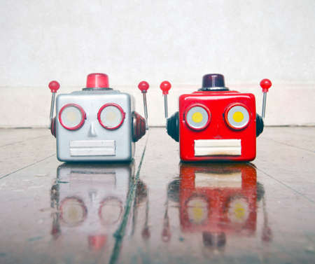 two metal robot heads chatting on a wooden floor with copy space, Stock fotó