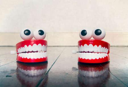 Deux jouets de dents en plastique discutant sur un vieux plancher en bois avec réflexion Banque d'images