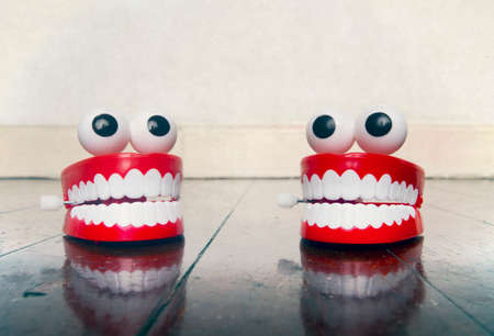 two platic teeth toys chatting on a old wooden floor with reflection Archivio Fotografico