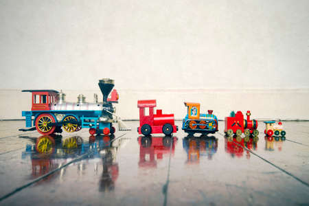 a line of vintage toy trains on a old wooden floor with copy space