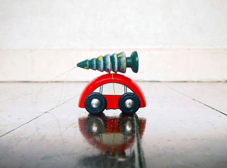 little red wooden toy car  with a Chrismas tree on a old wooden floor with copy space