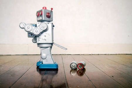 retro robot has a power failure  on a old wooden floor