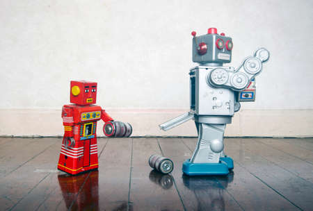 red robot helping big silver robot with a power problem Stock Photo