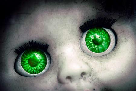Imagen macro de una vieja muñeca espeluznante, s ojos verdes Foto de archivo