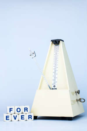 Classic Yellow Metronome with Alphabet Blocks say FOREVER in White Isolated Background Stock Photo