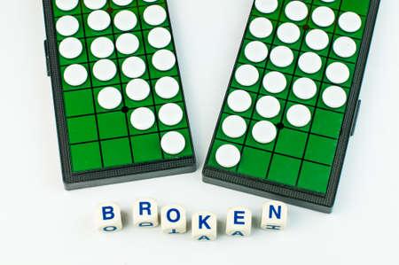 White Broken Heart Othellos on Separated Green Grid Othello Board with Alphabet Blocks say BORKEN Isolated Stock Photo