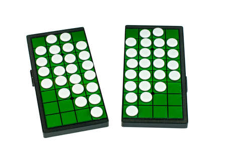 broken strategy: White Broken Heart Shaped Othellos on Separated Green Grid Othello Board Isolated Stock Photo
