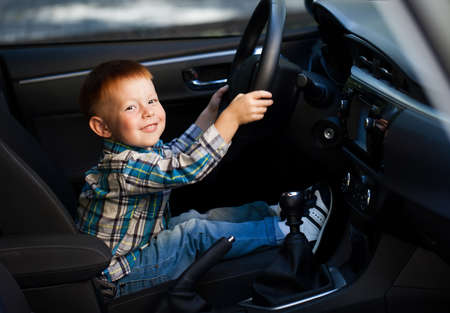 Cute little boy smiling and driving fathers car
