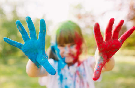 closeup of hands painted in the colors of Holi festival