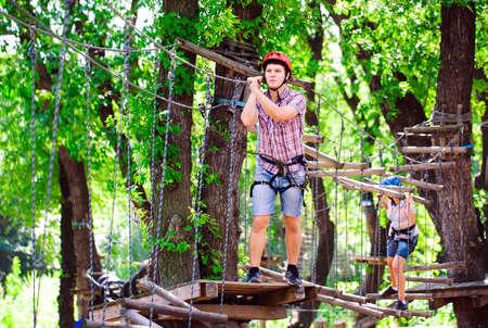 wspinaczka przygodowa high wire park - ludzie na kursie w kasku górskim i sprzęcie ochronnym