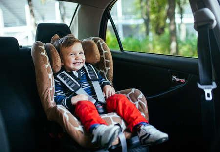 Schattige babyjongen in een autostoeltje.