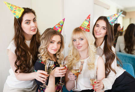 Girls congratulating friend on her birthday with glasses of champagne in hand.