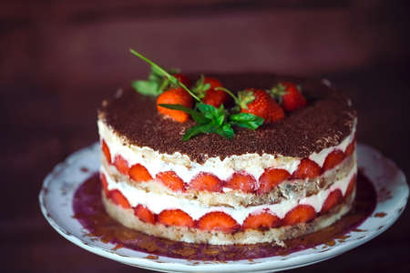 Strawberry cake as sweet treat and dessert on a wooden background. Standard-Bild