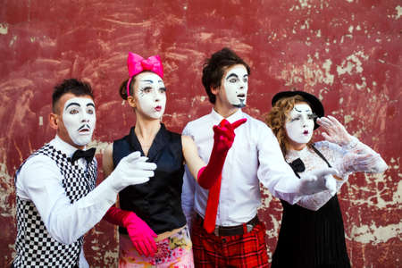Four mimes looking aside on the background of a red wall Stock fotó