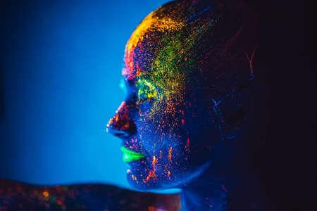 Meisje gekleurd fluorescerend poeder op een blauwe achtergrond.