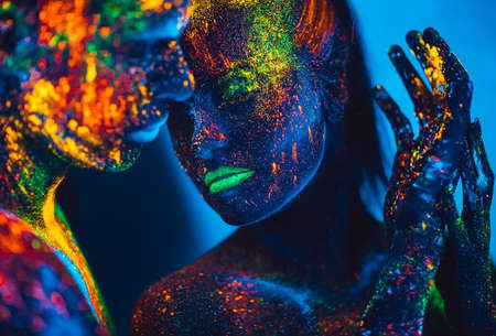 People are colored fluorescent powder. a pair of lovers dancing at a disco.