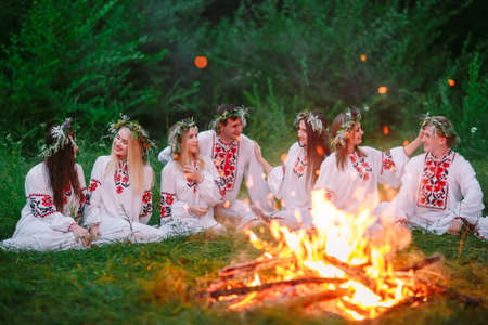 Midsummer night. Young people in Slavic clothes sitting near the bonfire