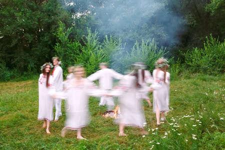 Milieu de l'été. Des jeunes en vêtements slaves tournent autour d'un feu en plein été