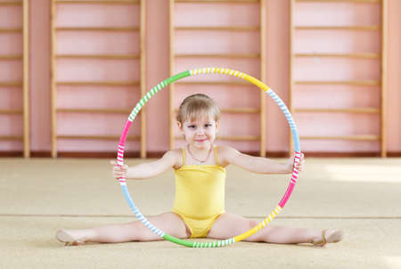 Chica joven haciendo gimnasia en el gimnasio.